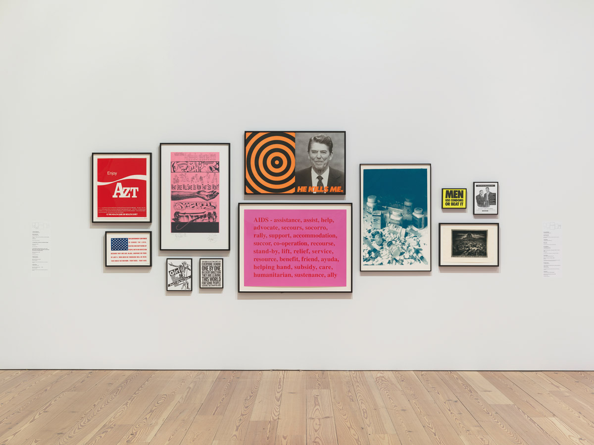 "fig. 3: Installation view of An Incomplete History of Protest: Selections from the 	Whitney's Collection, 1940-2017 (Whitney Museum of American Art, New York, August 18, 2017–). From left to right, top to bottom: Vincent Gagliostro and Avram Finkelstein, Enjoy AZT, 1989; Joseph Wolin, Tom Starace, and Richard Deagle, American Flag, 1989; John Ahearn, Andrew Castrucci, John ""Crash"" Matos, Chris ""Daze"" Ellis, Jane Dickson, Jenny Holzer,  Gary Simmons, and Martin Wong, The Usual Suspects, 1996; Barbara Kruger, (Girl don't die for love), 1992; John Giorno, The world is getting empty…, 1993; Donald Moffett, He Kills Me, 1987; Kay Rosen, AIDS, 1994; Frank Moore, trial proof and study for the poster FACE IT—LICK IT, 1992; Gran Fury,  (Men use condoms or beat it), 1988; Glenn Ligon, (Who will keep their dreams alive if we don't wake up to reality?), 1992; Sue Coe, Aids and the Federal Government, 1990. Photograph by Ron Amstutz. Digital image © Whitney Museum of American Art, New York."